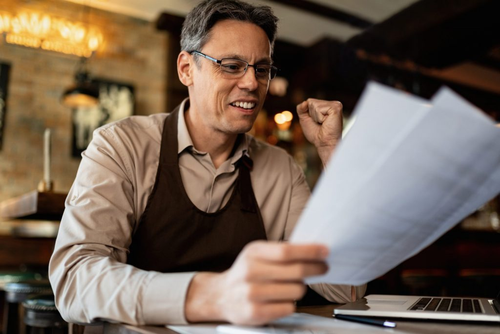 Middle-aged male barista analyzes paperwork.