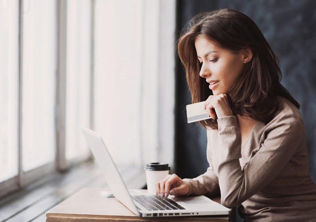 A brunette woman in a tan sweater holds her credit card while she online shops at her computer.