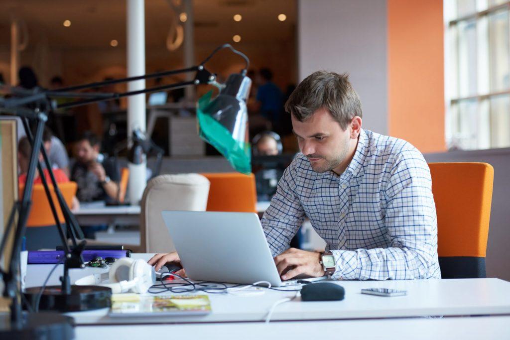 Software developer wearing a dress shirt works on laptop in a startup environment.