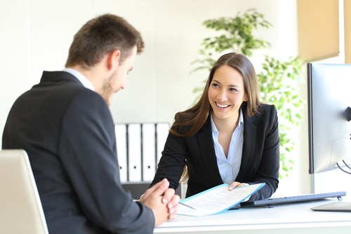 Smiling wholesale insurance broker business woman going over insurance documents with client at desk.