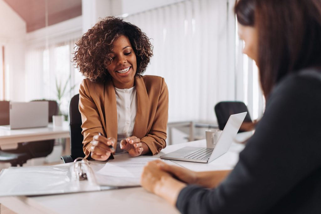 An African American client consults with her female insurance professional.