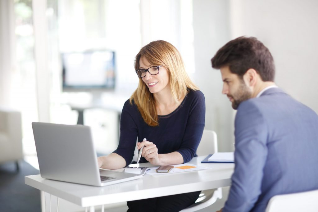 A blonde, female insurance professional shows her male client information on her white laptop.