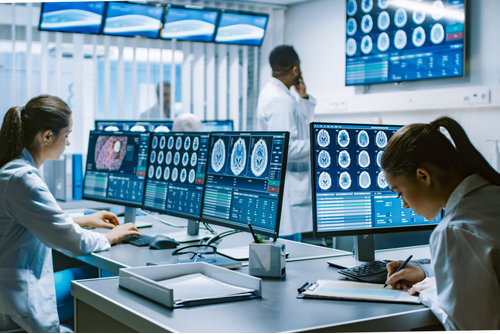 Team of doctors in front of computer monitors looking at brain scan images.