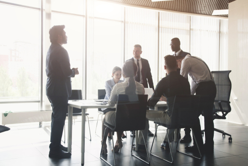 A group of seven business professionals gather around a conference table, some sitting, some standing.