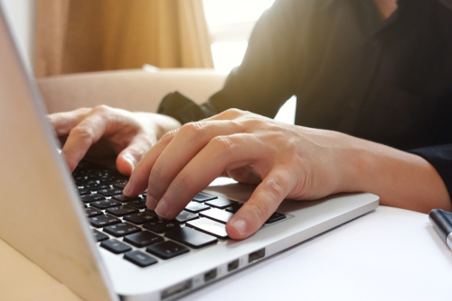 Close-up of a man in a black shirt with his hands typing on a silver laptop.