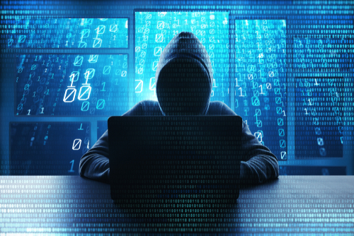 A cybercriminal in a dark hoodie sits in front of a laptop with blue code overlaying the image.