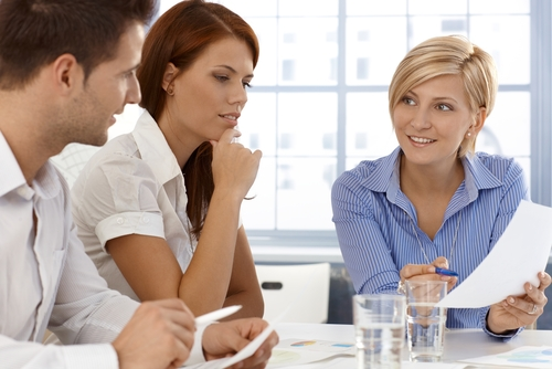 Business team in discussion of work document, working together in office