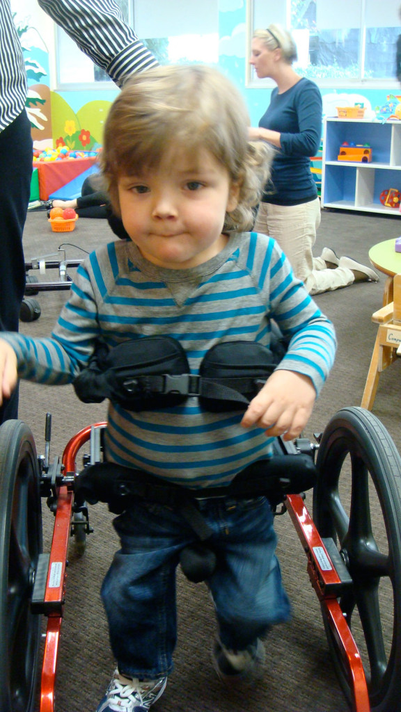 Vaughn, the namesake of the Love, Vaughn Foundation, smiles at the camera as he walks in his wheelchair.