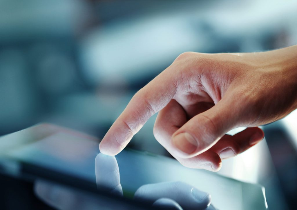 Close up of a hand touching an electronic tablet.