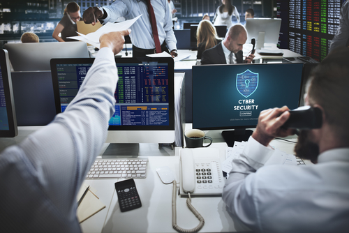 Office with busy workers and computer screen showing cybersecurity firewall.