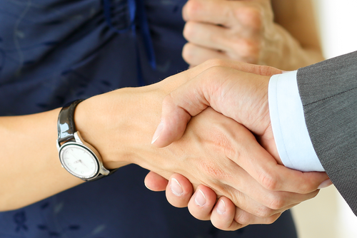 Close up of a handshake between a woman in a blue dress and a man in a grey suit.