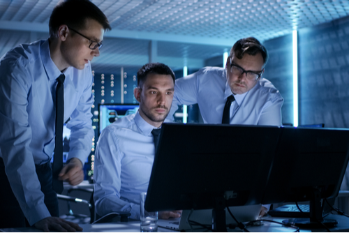 Three network security professionals in business attire are working to set up security in the system control room.