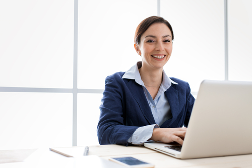 Smiling young business woman with brown hair and blue suit jacket sits at laptop computer.