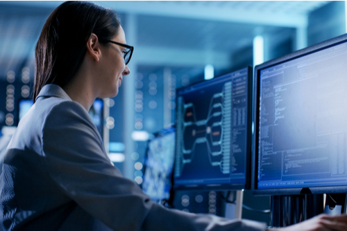 Female cybersecurity professional works in control room with dual monitors.