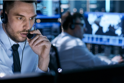 Technology support professional with- hands-free communication gear monitors cyber threats in the control room.