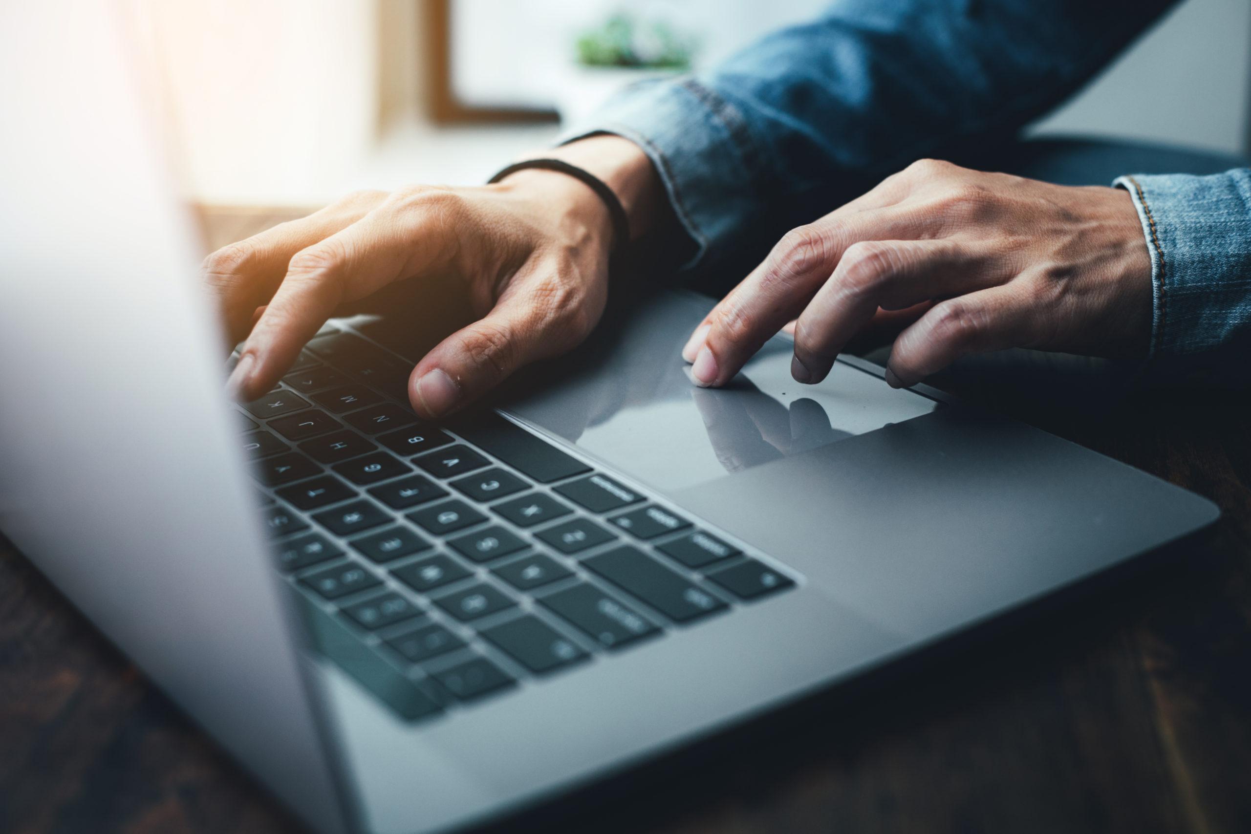 Older man hands typing on computer.