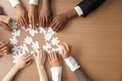 Close up of five sets of hands from employees of varying ethnicities and genders all reach for white puzzle pieces.