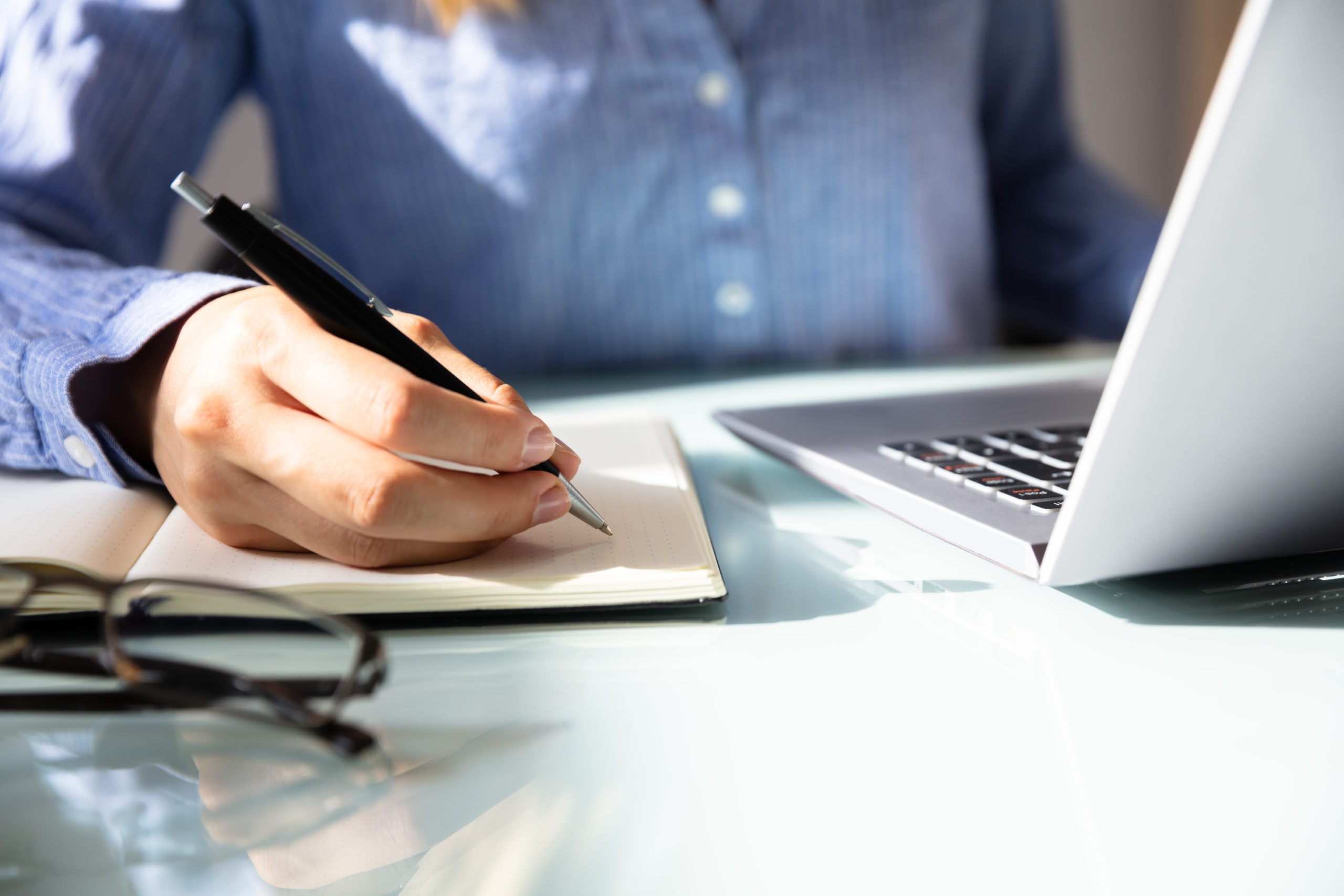 Closeup of businesswoman's hand taking notes next to a computer