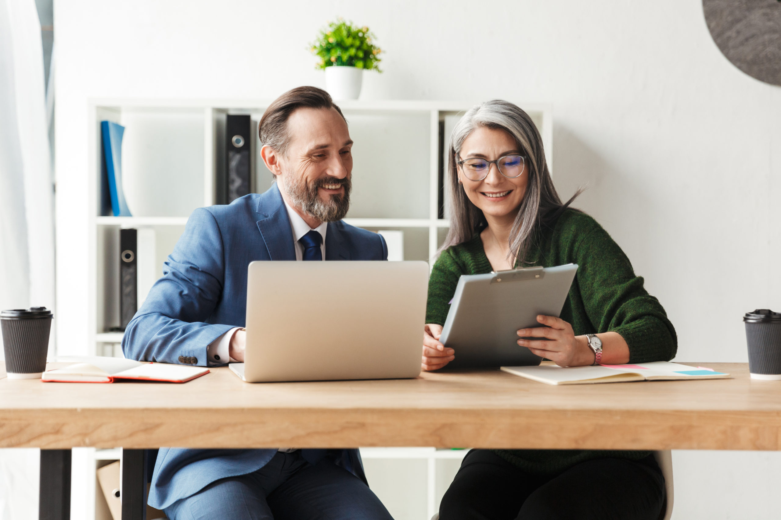 Adults smiling colleagues talking while working with laptop and documents in office
