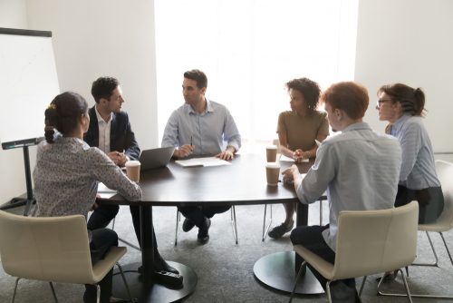 A group of three female and three male professionals sit at a round table discussing work.