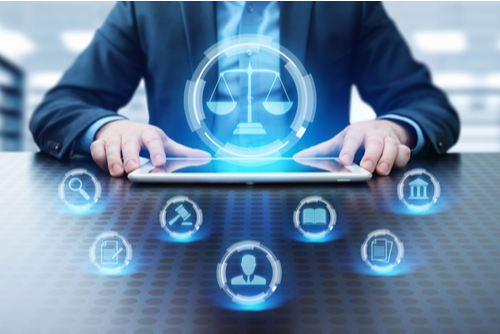 Labor law and lawyer concept, with man sitting at table as icons pop up in the air over tablet.