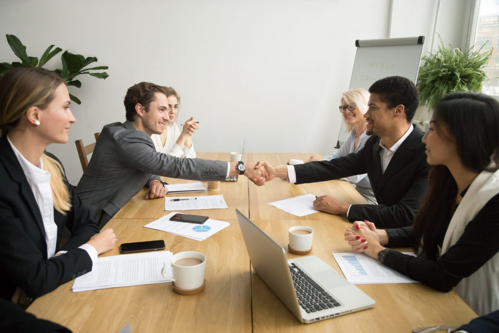 Diverse group of businesspeople at long wooden table with two shaking hands.