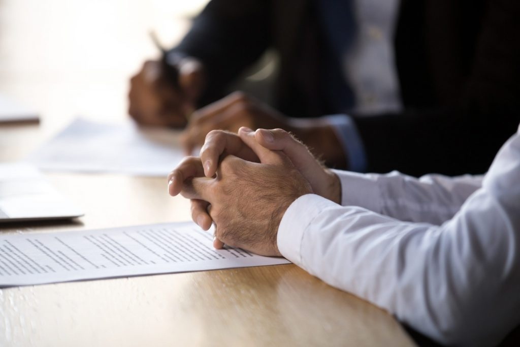 Male lawyer clasps hands on table while consulting with a client.