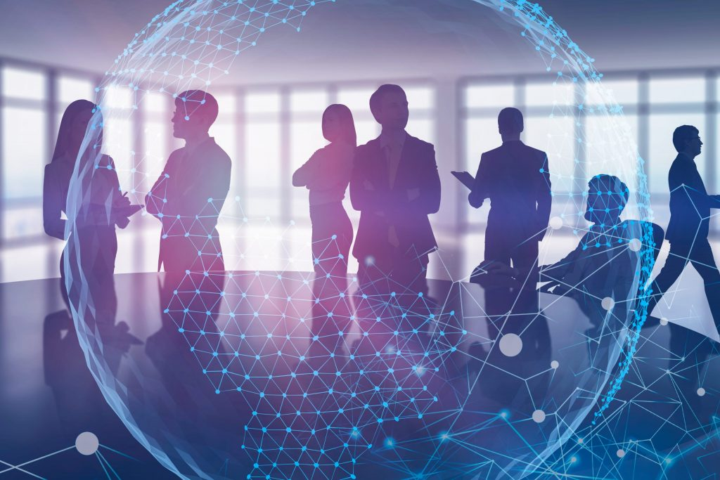 Silhouettes of business professionals in an office with a digital globe overlaying the image.