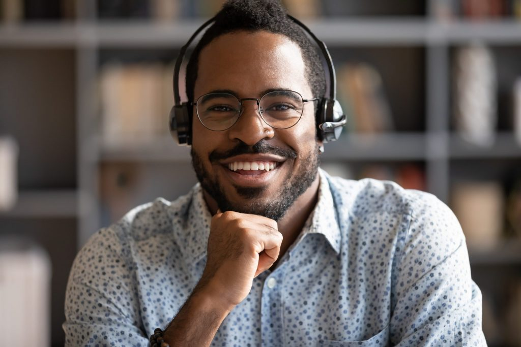 A smiling African American male leans on his hand while he takes a phone call from his headset at his desk.