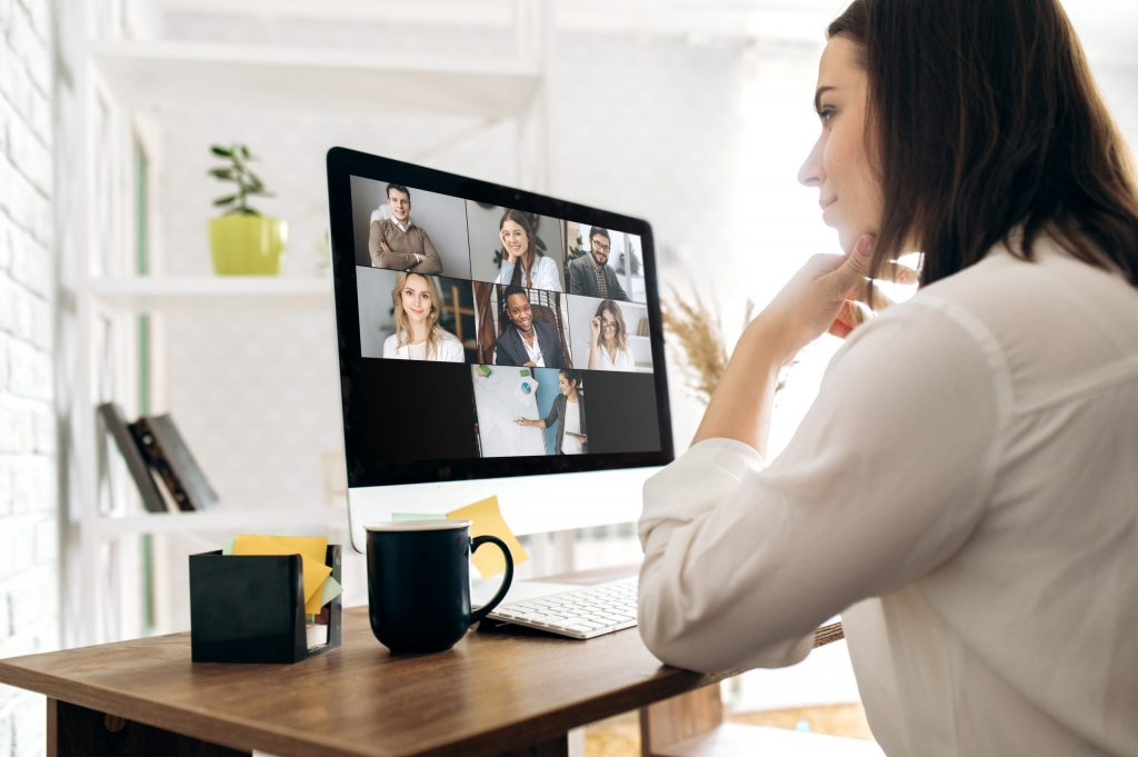 A young woman with brown hair wearing a white button-down holds a virtual meeting from her home office.
