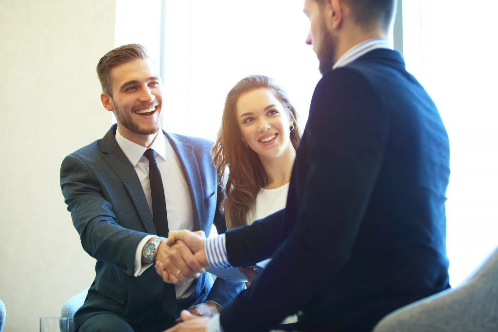 Three business professionals (two male and one female) smile and shake hands in a conference room.