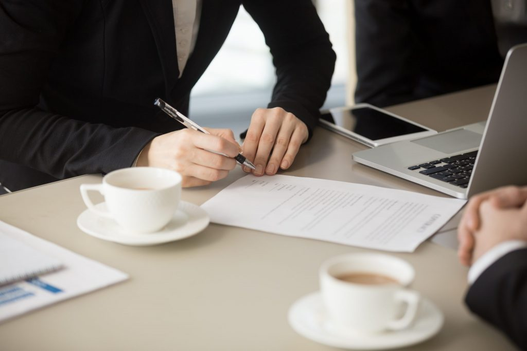 Female hand signing a paper with coffee cups, a laptop, and a cell phone on the table.