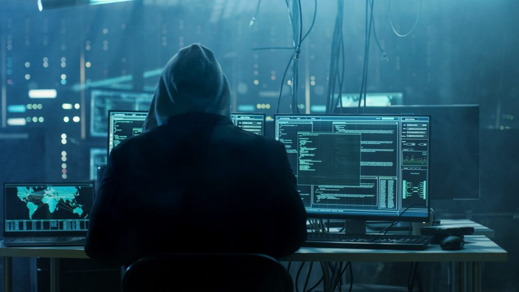 The back of a hacker in a black hoodie as he types code into a desktop computer in an IT room.