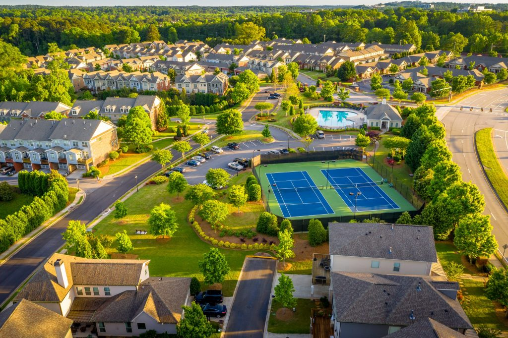 Aerial view of a well-manicured condo community with tennis courts and a pool.