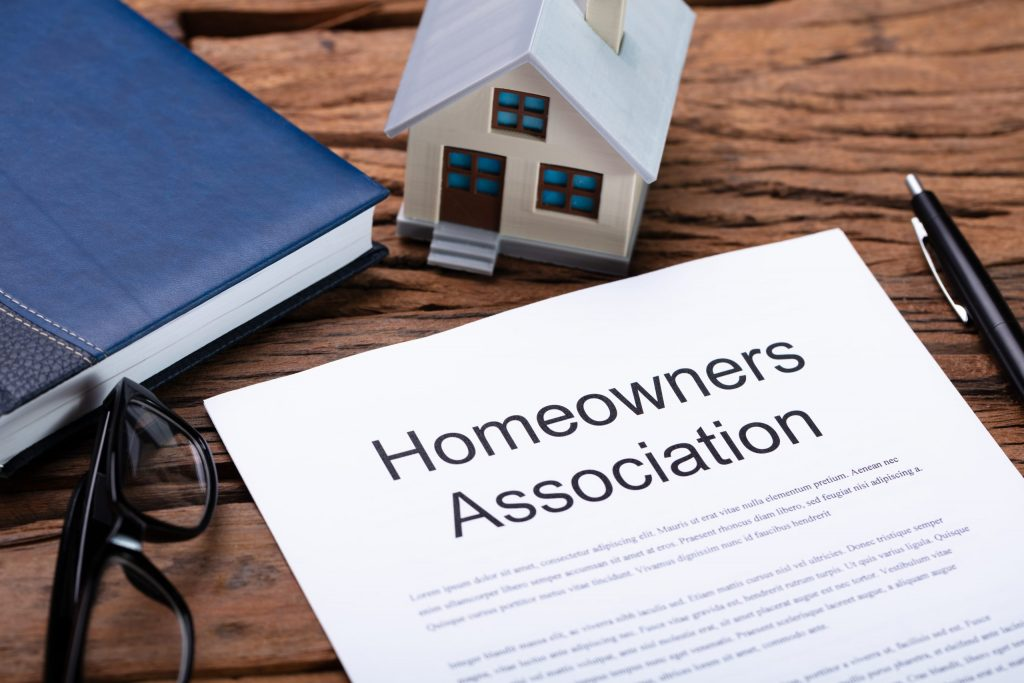 Close up of a homeowners association contract lying on a desk with a pen and small figurine of a house.