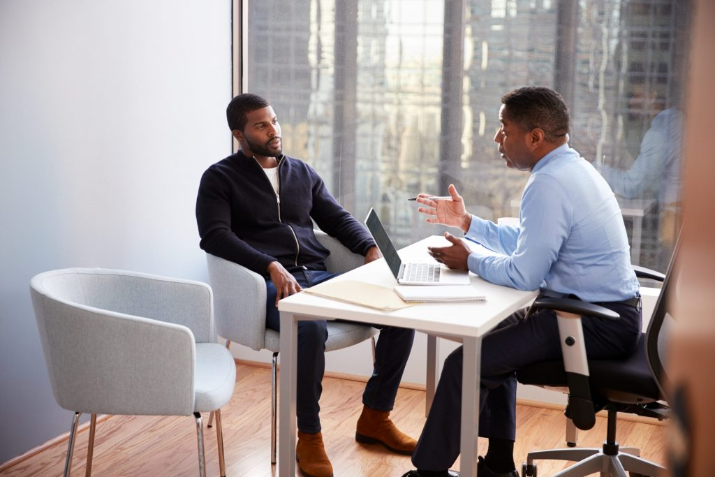 An African American business professional sits at his desk across from an African American client wearing a black sweater.