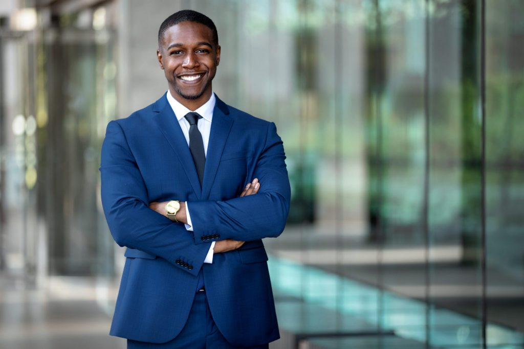 A young African American businessman wears a navy suit and smiles with his arms crossed.