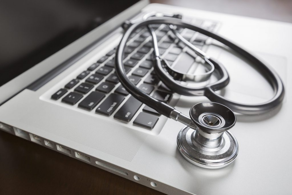 A stethoscope lays on the keyboard of a silver laptop.