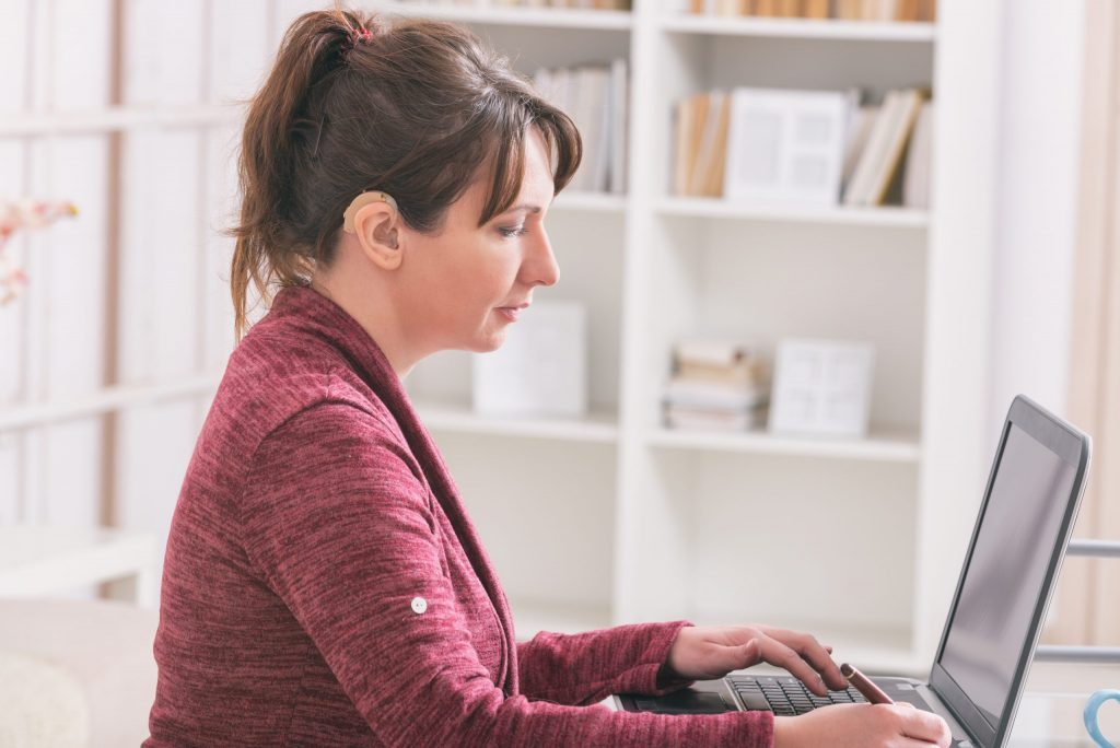 A hearing-impaired woman with a hearing aid sits at a desk and works on a laptop.