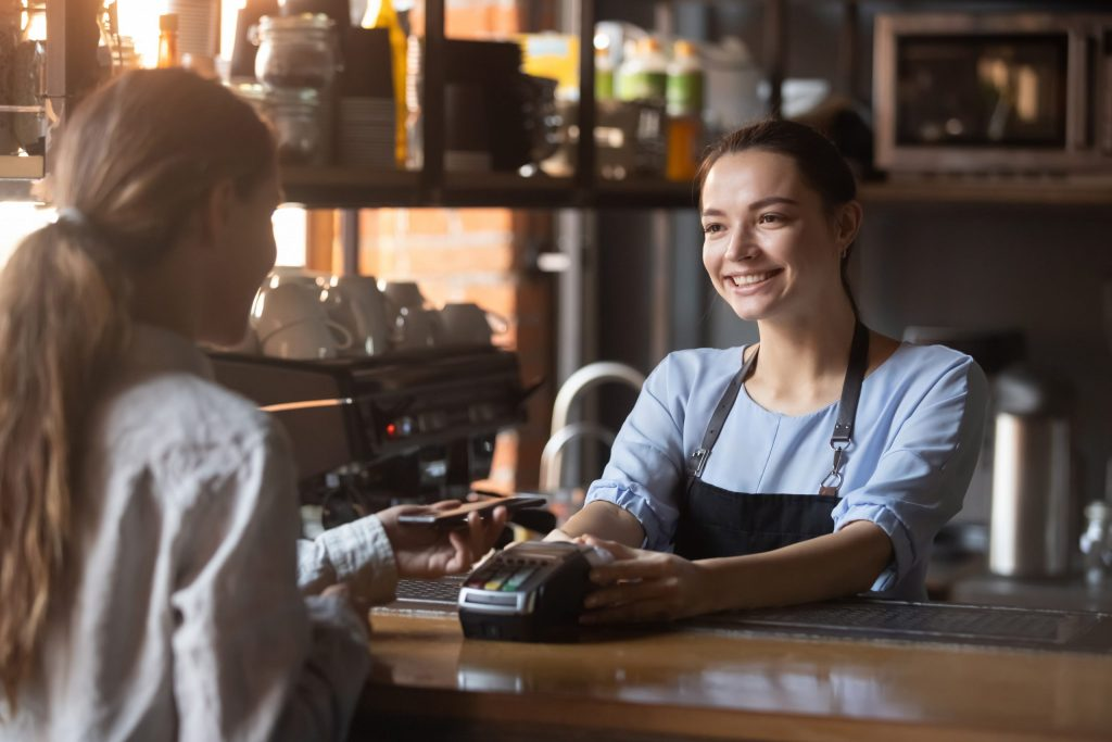 A smiling young female cashier holds a point of sale system out to a young female customer to tap and pay with her phone.