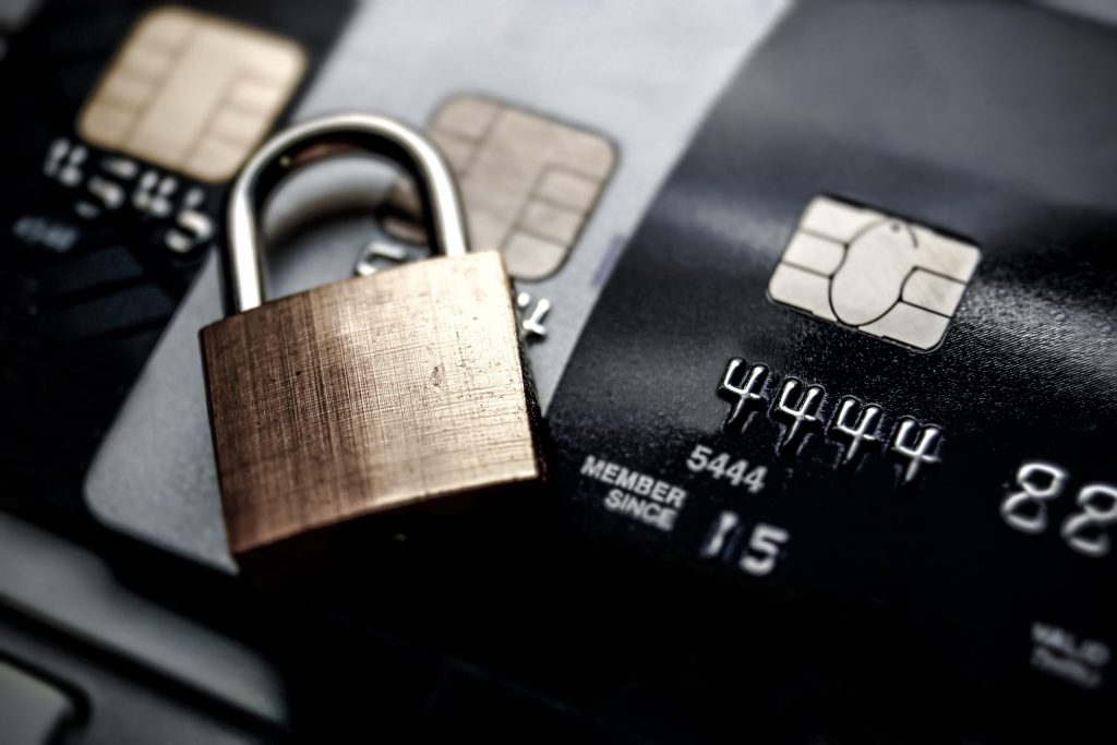 Close up of the microchip on three credit cards with a gold padlock laying on top of the credit cards.
