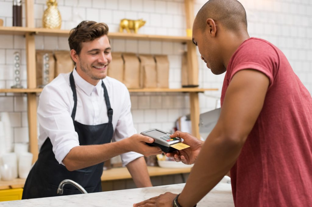 A male cashier holds a point of sale system to a male customer in a red shirt who inserts his credit card to pay.
