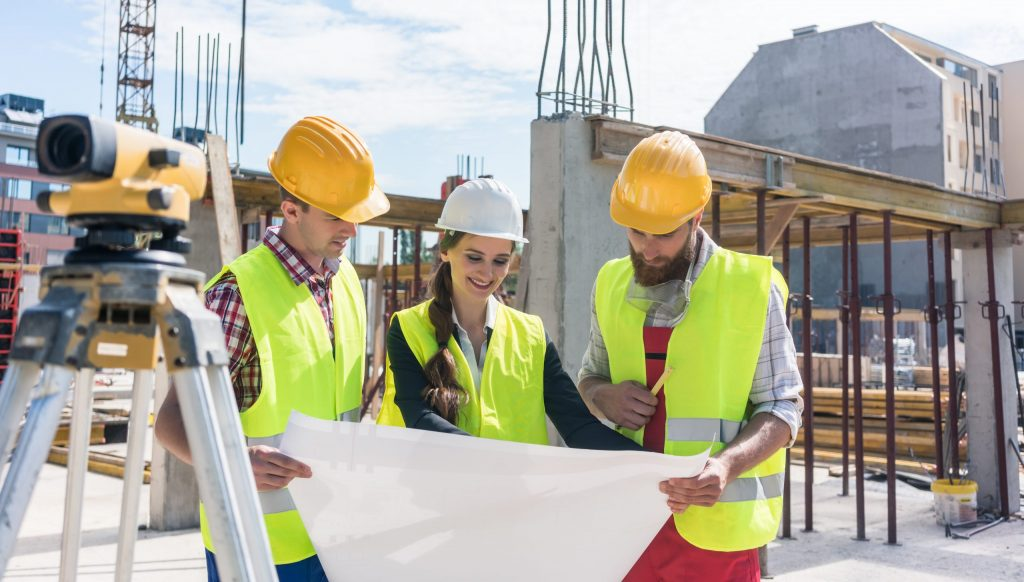 Female architect holds and discusses blueprint with two male construction managers at site, all wearing hard hats.