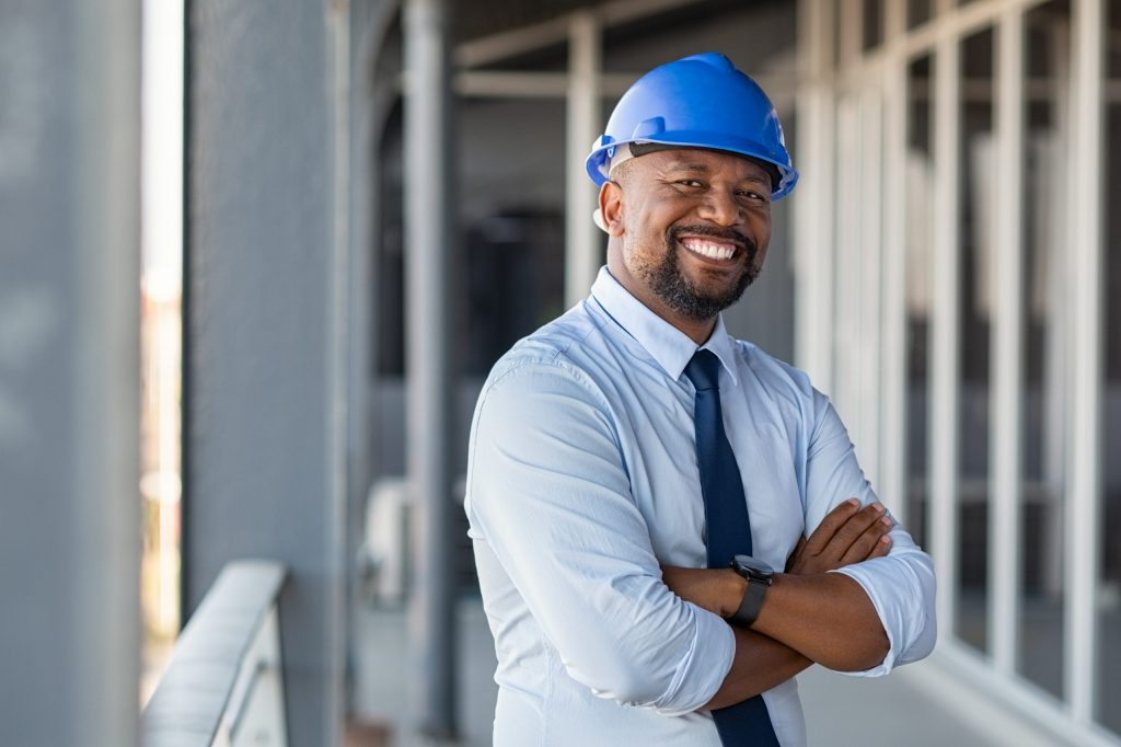 Male architect wearing hard hat stands at construction site, smiling with arms folded across his chest.