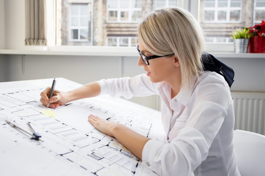 Female architect sits at her angled drafting table in her home, sketching a blueprint.